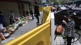 Salah satu pedagang yang bertahan dari balik tembok mengatakan usahanya tetap berjalan dengan transaksi terjadi dari sisi berbeda dengan pembeli.(AP Photo/Ng Han Guan)