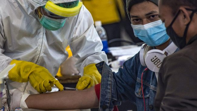 Indonesian officials conduct health screening on 156 migrant workers who arrived from Malaysia at Surabaya airport in Indonesia's East Java on April 7, 2020, amid concerns of the spread of the COVID-19 coronavirus. (Photo by Juni Kriswanto / AFP)