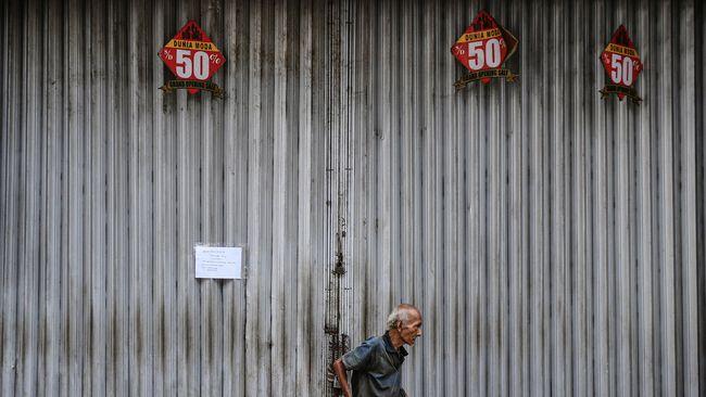 Seorang pria melintasi deretan toko yang tutup di Pasar Baru, Jakarta, Rabu (1/4/2020). Menteri Keuangan Sri Mulyani menyatakan pertumbuhan ekonomi Indonesia tahun 2020 akan turun menjadi 2,3 persen dan dalam skenario terburuk bahkan bisa mencapai -0,4 persen akibat dampak dari pandemi COVID-19. ANTARA FOTO/Akbar Nugroho Gumay/foc.