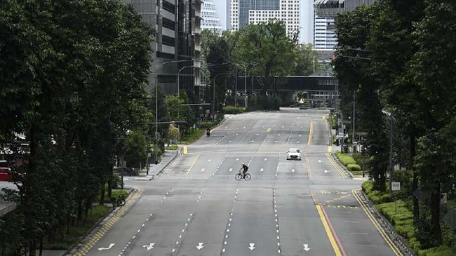 A cyclist rides across a quiet street in the central business district of Singapore on April 7, 2020, as the country ordered the closure of all businesses deemed non-essential as well as schools to combat the spread of the COVID-19 novel coronavirus. - Singapore's usually bustling business district was almost deserted on April 7 as most workplaces in the city-state closed to stem the spread of the coronavirus after a surge in cases. (Photo by Roslan RAHMAN / AFP)