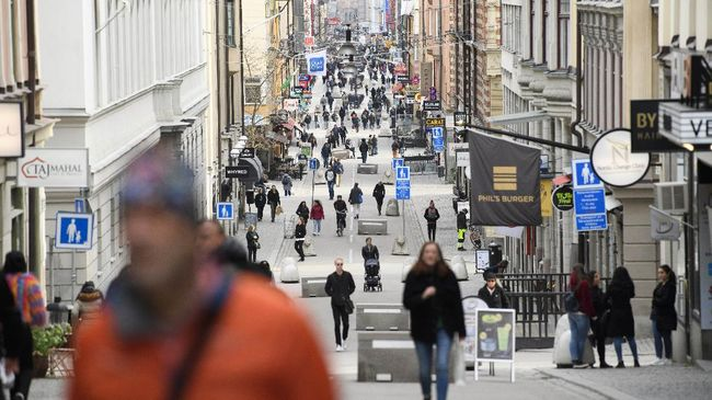 In this photo taken on March 27, 2020, people go about their daily routing, on Drottninggatan, the main shopping street in Stockholm, Sweden, amid the new coronavirus COVID-19 pandemic. The coronavirus is not keeping people in Sweden at home even while citizens in many parts of the world are sheltering in place. Swedes still sit at outdoor cafes in the center of Stockholm. (Henrik Montgomery/TT News Agency via AP)