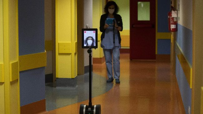 Nurse Helga drives 'Ivo' a tablet supported by a periscopic pole mounted on wheels at 'Ospedale di Circolo' in Varese, Italy, Wednesday, April 8, 2020. Ivo is remotely controlled by the healthcare professional via smartphone. It can enter the rooms and, with a video call system, put the staff in communication with the patients. The new coronavirus causes mild or moderate symptoms for most people, but for some, especially older adults and people with existing health problems, it can cause more severe illness or death. (AP Photo/Luca Bruno)