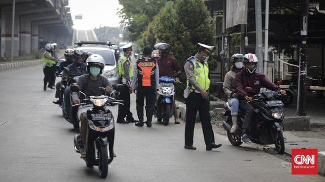 Polisi dan petugas dishub melakukan sosialisasi penggunaan masker dan tidak boleh motor berboncengan, Jakarta.