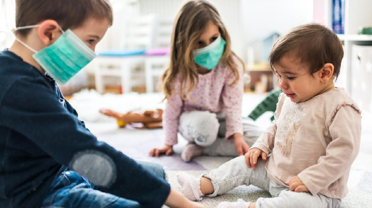 Little children wearing pollution masks at home. Two toddler kids are wearing masks while baby is crying and it's hard to put mask on her face.