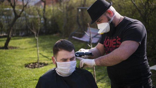 Kosovo hairdresser Driton Kameri (R) wears a facemask as he cuts the hair of a client in his garden on March 30, 2020 in Pristina during the time of COVID-19 pandemic. - In Pristina, a barber is defying coronavirus edits, such as the ban on opening non-essential shops, to practice his art in the open air, but not without first spraying his customers with disinfectant from head to toe. (Photo by Armend NIMANI / AFP)