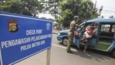 Petugas Satpol PP menghentikan angkot yang tidak mengikuti aturan PSBB saat memasuki kawasan Jakarta di Jalan Raya Bogor, Jakarta Timur, Jumat (10/4/2020). Pengawasan di perbatasan Jakarta dengan Kota Depok tersebut dalam rangka penerapan Pembatasan Sosial Berskala Besar (PSBB) di DKI Jakarta selama 14 hari dimulai pada 10 April hingga 23 April 2020. ANTARA FOTO/Asprilla Dwi Adha/pras.