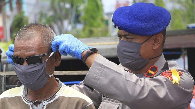 Personel Kepolisian Polres Aceh Barat memasangkan masker ke pengguna jalan saat proses pembagian masker di Meulaboh, Aceh Barat, Aceh, Selasa (14/4/2020). Pihak Kepolisian bersama Bhayangkari setempat telah membagikan 1200 masker kepada masyarakat dalam rangka mendukung imbauan Pemerintah agar masyarakat menggunakan masker saat berada di luar rumah untuk mengurangi penyebaran dan penularan COVID-19. ANTARA FOTO/Syifa Yulinnas/hp.