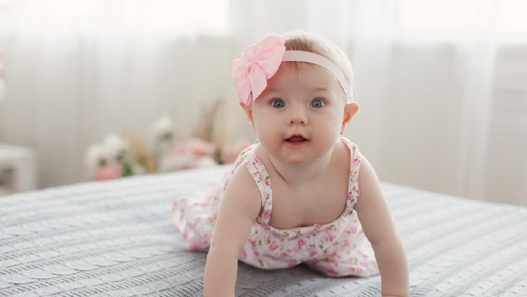 Charming beautiful lovely small female baby with plump cheeks creeps on bed, looks innocently on something, being naughty. Cute baby infant plays alone. Newborn kid crawls. Enthusiastic child
