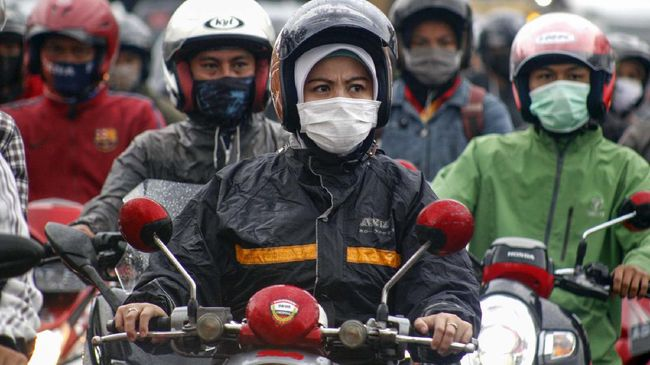 Sejumlah pengendara menggunakan masker saaat berkendara di Cibinong, Kabupaten Bogor,  Jawa Barat, Selasa (14/4/2020). Saat penerapan Pembatasan Sosial Berskala Besar (PSBB) selama 14 hari, salah satu aturannya adalah pembatasan penumpang kendaraan serta anjuran untuk menggunakan masker jika berkendaraan. ANTARA FOTO/Yulius Satria Wijaya/hp.