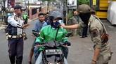 Petugas memeriksa suhu tubuh warga yang melintas di Jalan Bintara Raya, Bekasi, Jawa Barat, Sabtu (4/4/2020). Pemerintah Kota (Pemkot) menjaga ketat pergerakan masyarakat yang akan masuk ke Kota Bekasi dengan memeriksa suhu tubuh di wilayah perbatasan guna mencegah dan memutus penyebaran pandemi COVID-19. ANTARA FOTO/Suwandy/hp.