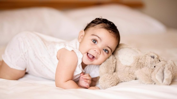 Cute little baby boy with little rabbit in bed after bath, baby after shower, cute child smiling at camera, bunny hext to  him