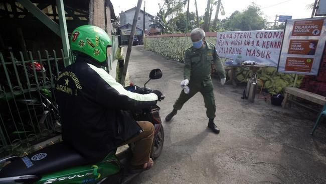Petugas Linmas menyemprotkan cairan disinfektan saat memasuki RW Siaga di Desa Palasari, Citeureup, Kabupaten Bogor,  Jawa Barat, Rabu (15/4/2020). Pemkab Bogor mengajak seluruh pihak aktif mencegah penyebaran virus Corona (COVID-19), salah satunya membentuk satgas di tingkat RW untuk mencegah penyebaran virus tersebut. ANTARA FOTO/Yulius Satria Wijaya/aww.