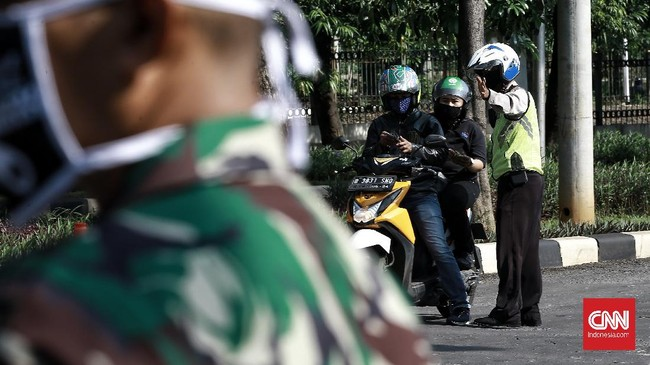 Aparat  melakukan pemeriksaan pengendara roda dua dan empat di Jalan akses UI, Depok pemeriksaan bertujuan menghimbau pengendara untuk menggunakan masker dan peraturan posisi duduk dan jumlah penumpang selama PSBB. Depok (15/4/2020). Polda Metro Jaya membangun 20 titik pos di perbatasan Depok untuk mengawasi kendaraan yang keluar masuk Ibu Kota selama masa pembatasan sosial berskala besar atau PSBB. CNN Indonesia/Andry Novelino