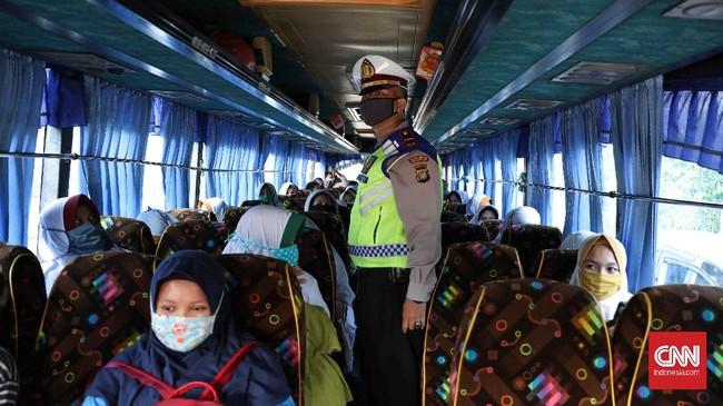 Polisi memeriksa bus karyawan yang tidak tertib aturan PSBB di pintu tol keluar Bekasi, Jawa Barat, Rabu, 15 April 2020. Pembatasan Sosial Berskala Besar (PSBB)  dimulai hari ini di Kota Bekasi hingga 28 April 2020. CNNIndonesia/Safir Makki