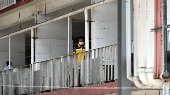 A foreign worker, wearing face mask as a preventive measure against the spread of the COVID-19 novel coronavirus, looks out from a window of the workers' dormitory in Singapore on April 9, 2020. - Migrant workers in Singapore are living in fear following a surge of coronavirus infections in their dormitories where they say cramped and filthy conditions make social distancing impossible. (Photo by Roslan RAHMAN / AFP) / TO GO WITH Health-virus-Singapore-migration, FOCUS by Catherine Lai and Sam Reeves