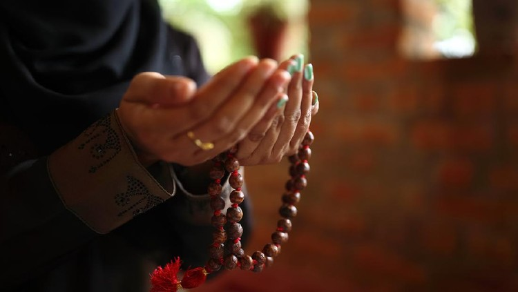 Close-up shot of a Muslim woman's hands holding rosary.