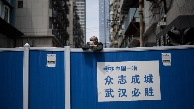 A man wearing a face mask looks over a barricade set up to keep people out of a residential compound in Wuhan in China's central Hubei province on April 14, 2020. (Photo by NOEL CELIS / AFP)