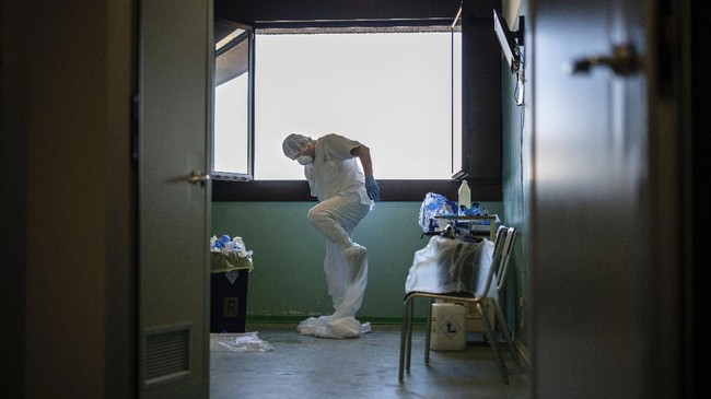 Doctor Giovanni Passeri takes his protective gear off at the end of a night shift in his ward inside the COVID-19 section of the Maggiore Hospital in Parma, northern Italy Thursday, April 9, 2020. Undressing the three layers of protection requires extreme caution, Passeri says, to ensure nothing contaminated by the virus will touch his skin. (AP Photo/Domenico Stinellis)