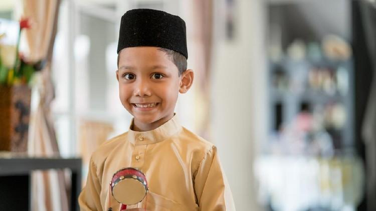Young boy wearing traditional clothes looking excited in anticipation of the Islamic celebration of Hari Raya Aidilfitri (Eid al-Fitr). Kuala Lumpur, Malaysia. May 2018