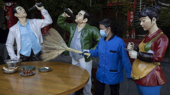 A cleaner wearing a mask to help stop the spread the coronavirus sweeps replicas of food and statues depicting normal life along a retail street in Wuhan, central China's Hubei province,  Thursday, April 9, 2020. Released from their apartments after a 2 1/2-month quarantine, residents of the city where the coronavirus pandemic began are cautiously returning to shopping and strolling in the street but say they still go out little and keep children home while they wait for schools to reopen. (AP Photo/Ng Han Guan)