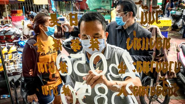 An employee wearing a face mask amid fears of the spread of COVID-19 coronavirus paints the new prices of gold on the shop window of a goldsmith as another employee checks the temperature of a customer in Bangkok's Chinatown on April 15, 2020. - Hundreds of Bangkok residents rushed to goldsmith shops in order to sell their jewelries as gold prices reached its highest levels since 2012. (Photo by Mladen ANTONOV / AFP)