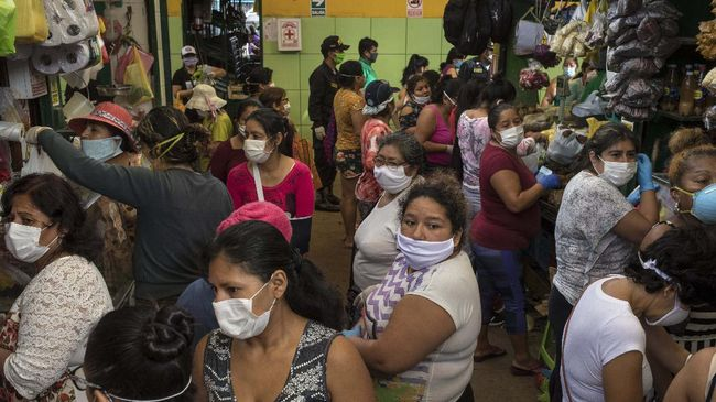 Women, wearing protective face masks, wait to buy food at a popular market in Lima, Peru, Saturday, April 4, 2020. Due to the health emergency from the spread of the new coronavirus, the government is restricting people's movement by gender, with Saturday designated to women, who can leave home to buy basic necessities. (AP Photo/Rodrigo Abd)