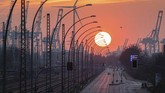 The sun sets behind an industrial city-scape in the port of Hamburg, Germany, Saturday April 11, 2020.  The COVID-19 coronavirus causes less serious symptoms for most people, but for some, especially older adults and people with existing health problems, it can cause severe illness and even death.(Daniel Reinhardt/dpa via AP)