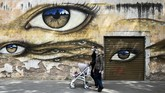A couple wearing face masks and pushing a pram walks past a mural in the Trastevere district of Rome on April 13, 2020 during the country's lockdown aimed at curbing the spread of the COVID-19 infection, caused by the novel coronavirus. (Photo by Vincenzo PINTO / AFP)