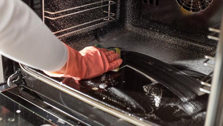 Close up of female hands with protective gloves scrubbing oven in kitchen