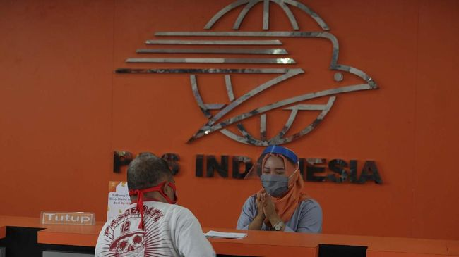 Karyawan Kantor Pos Indonesia Solo memakai Alat Pelindung Diri (APD) jenis Face Shield atau pelindung wajah saat melayani pelanggan di Solo, Jawa Tengah, Senin (20/4/2020). Kebijakan Pos Indonesia Solo tersebut untuk memberikan perlindungan maksimal kepada karyawan, keluarganya, dan bahkan pelanggan dari kemungkinan terpapar COVID-19 yang kini telah menjadi pandemi global. ANTARA FOTO/Maulana Surya/hp.