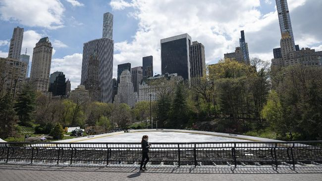 A woman wearing a mask walks in the almost deserted Central Park in Manhattan on April 16, 2020 in New York City. - Gone are the softball games, horse-drawn carriages and hordes of tourists. In their place, pronounced birdsong, solitary walks and renewed appreciation for Central Park's beauty during New York's coronavirus lockdown. The 843-acre (341-hectare) park -- arguably the world's most famous urban green space -- normally bustles with human activity as winter turns to spring, but this year due to Covid-19 it's the wildlife that is coming out to play. (Photo by Johannes EISELE / AFP)