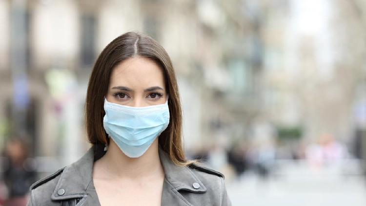Front view portrait of serious woman with protective mask avoiding contagion looking at camera on street