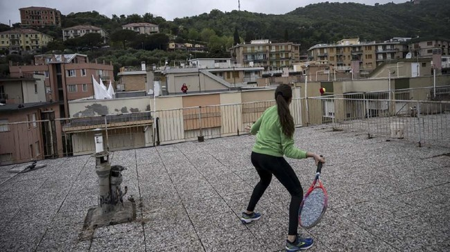 Vittoria Oliveri (front) plays tennis with Carola in background on rooftops of their house in Finale Ligure, Liguria Region, northwestern Italy on April 19, 2020, during the country's lockdown aimed at stopping the spread of the COVID-19 (new coronavirus) pandemic. - Everyday Carola, 11, and Vittoria, 13, play tennis from a rooftop to another rooftop of their homes to practice during the Covid 19 lockdown. (Photo by MARCO BERTORELLO / AFP)