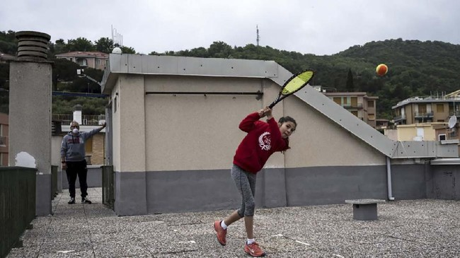 Carola Pessina (R) plays tennis with Vittoria Oliveri (unseen) undert he look of her father on the rooftops of their house in Finale Ligure, Liguria Region, northwestern Italy on April 19, 2020, during the country's lockdown aimed at stopping the spread of the COVID-19 (new coronavirus) pandemic. - Everyday Carola Pessina, 11, and Vittoria Oliveri, 13, play tennis from a rooftop to another rooftop of their homes to practice during the Covid 19 lockdown. (Photo by MARCO BERTORELLO / AFP)