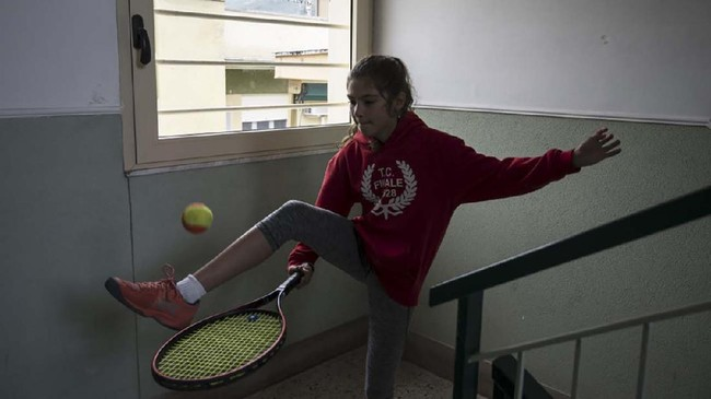 Carola Pessina practices tennis in the staircase before playing with Vittoria Oliveri (unseen) on the rooftops of their house in Finale Ligure, Liguria Region, northwestern Italy on April 19, 2020, during the country's lockdown aimed at stopping the spread of the COVID-19 (new coronavirus) pandemic. - Everyday Carola Pessina, 11, and Vittoria Oliveri, 13, play tennis from a rooftop to another rooftop of their homes to practice during the Covid 19 lockdown. (Photo by MARCO BERTORELLO / AFP)