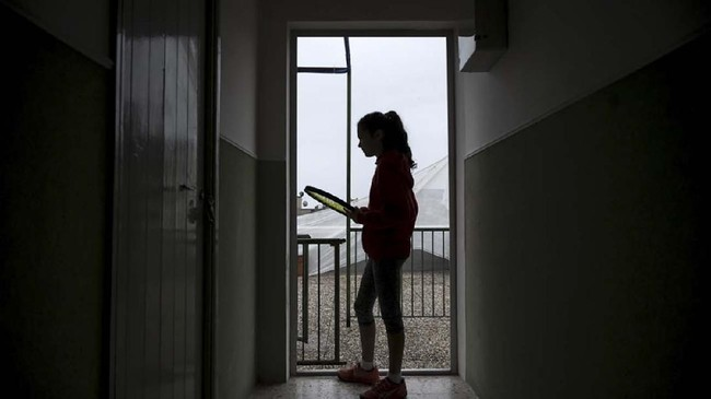 Carola Pessina is silouhetted before playing tennis with Vittoria Oliveri (unseen) on the rooftops of their house in Finale Ligure, Liguria Region, northwestern Italy on April 19, 2020, during the country's lockdown aimed at stopping the spread of the COVID-19 (new coronavirus) pandemic. - Everyday Carola Pessina, 11, and Vittoria Oliveri, 13, play tennis from a rooftop to another rooftop of their homes to practice during the Covid 19 lockdown. (Photo by MARCO BERTORELLO / AFP)