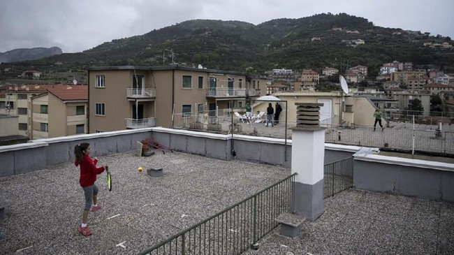 Carola Pessina (foreground) plays tennis with Vittoria Oliveri on the rooftops of their house in Finale Ligure, Liguria Region, northwestern Italy on April 19, 2020, during the country's lockdown aimed at stopping the spread of the COVID-19 (new coronavirus) pandemic. - Everyday Carola Pessina, 11, and Vittoria Oliveri, 13, play tennis from a rooftop to another rooftop of their homes to practice during the Covid 19 lockdown. (Photo by MARCO BERTORELLO / AFP)