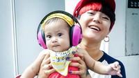 <p>Baby June juga pernah diajak kerja MamaPoppy nih. <em>Cute</em> banget sih pakai <em>headphone</em> pink gitu. (Foto: Instagram @popsovia)</p>