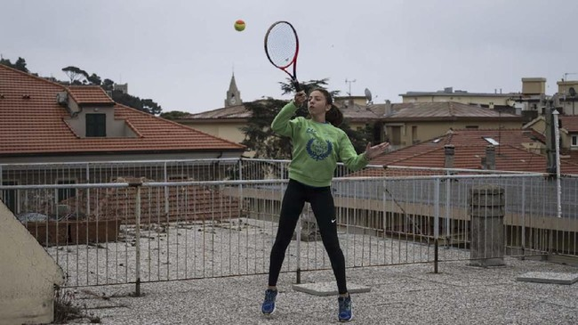 Vittoria Oliveri plays tennis with Carola (unseen) on rooftops of their house in Finale Ligure, Liguria Region, northwestern Italy on April 19, 2020, during the country's lockdown aimed at stopping the spread of the COVID-19 (new coronavirus) pandemic. - Everyday Carola, 11, and Vittoria, 13, play tennis from a rooftop to another rooftop of their homes to practice during the Covid 19 lockdown. (Photo by MARCO BERTORELLO / AFP)