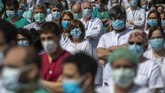 Health workers hold a minute of silence to remember Joaquin Diaz, the hospital's chief of surgery who died of COVID-19, at La Paz hospital in Madrid, Spain, Monday, April 20, 2020. The Spanish government is starting to relax its confinement measures due to the Covid-19 coronavirus outbreak, trying to re-activate the economy after a two-week freeze and allowing children under 12 years-old to venture out to the streets for brief periods from next week. (AP Photo/Manu Fernandez)