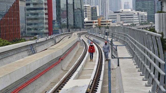 Dua pekerja melintasi rel di dekat Stasiun Kereta Api Ringan atau Lintas Rel Terpadu (LRT) Rasuna Said, Kuningan, Jakarta, Selasa (21/4/2020). Meski pembatasan sosial berskala besar (PSBB) berlangsung di tengah wabah virus corona (COVID-19) di Jakarta, proyek LRT Jabodebek yang per awal April 2020 mencapai 71,43 persen tersebut tetap berjalan dengan standar keamanan kesehatan yang lebih diperketat. ANTARA FOTO/Aditya Pradana Putra/hp.