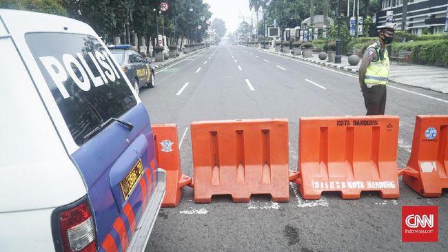 Petugas kepolisian berjaga di sekitaran Jalan Asia Afrika di hari pertama pelaksanaan PSBB, Rabu (22/4).
