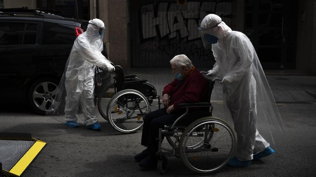 FILE - In this April 11, 2020, file photo, a volunteer of the Spanish NGO Open Arms pushes in a wheelchair an elderly resident of a nursing home with coronavirus symptoms to a Hospital in Barcelona. Countries across Europe are struggling amid the coronavirus pandemic with the dilemma of leaving the elderly and others near death in enforced solitude or whether to allow some personal contact with relatives. At nursing homes, everything is done to keep out visitors who might be infected, and family members are almost always banned from coming to see their loved ones. (AP Photo/Felipe Dana, File)