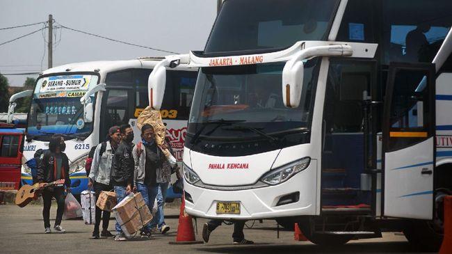 Sejumlah warga membawa barang bawaan menuju bis antar provinsi untuk mudik lebih awal di Terminal Bis Pakupatan, Serang, Banten, Kamis (23/4/2020). Meski pemerintah melarang mudik lebaran tahun 2020, sejumlah warga tetap pulang ke kampung halamannya sebelum puasa dengan alasan sudah tidak ada pekerjaan meski nantinya harus menjalani isolasi mandiri.  ANTARA FOTO/Asep Fathulrahman/nz