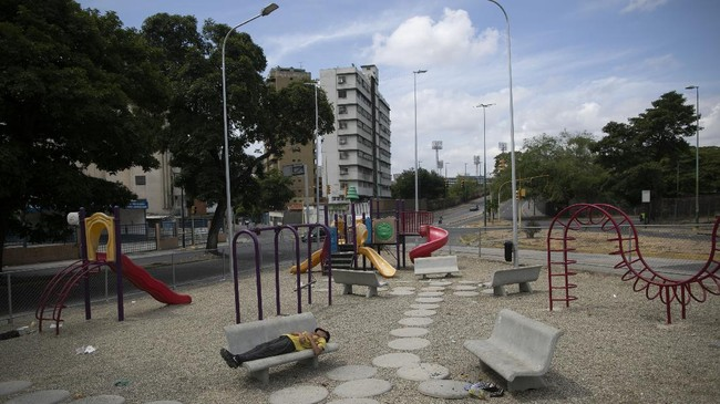 A man sleeps on a bench at a deserted playground amid a nationwide quarantine to slow the spread of the new coronavirus, in Caracas, Venezuela, Tuesday, April 7, 2020. (AP Photo/Ariana Cubillos)