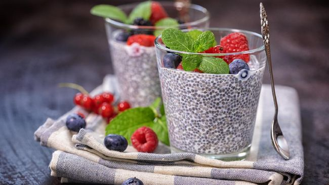 Two glasses of chia seed pudding with fresh berry fruits and mint topping for the breakfast