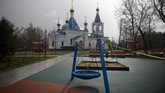 A caution tape cordons off an empty children's playground with an Orthodox church seen in the background, officially closed for parishioners according to the order of the city authorities due to coronavirus, in Moscow, Russia, April 18, 2020. (AP Photo/Alexander Zemlianichenko)