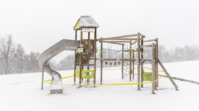 A playground covered in snow is closed at Normafa during during the coronavirus in Budapest, Hungary, March 23, 2020. (Marton Monus/MTI via AP)