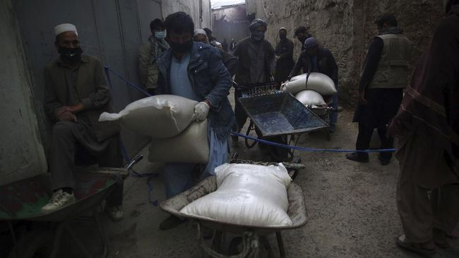 Daily-wage workers, receive free wheat donated by Afghan businessmen ahead of the upcoming holy fasting month of Ramadan in Kabul, Afghanistan, Monday, April 20, 2020. Muslims across the world are observing the holy fasting month of Ramadan, when they refrain from eating, drinking and smoking from dawn to dusk.(AP Photo/Rahmat Gul)