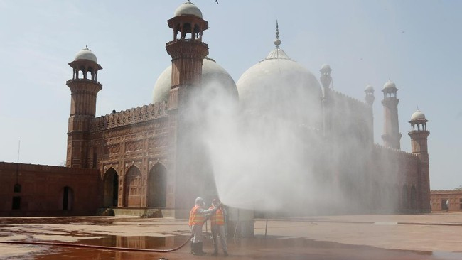 Volunteers disinfects the historical Badshahi Mosque ahead of the Muslim fasting month of Ramadan, in Lahore, Pakistan, Wednesday, April 22, 2020. Ramadan begins with the new moon later this week, Muslims all around the world are trying to work out how to maintain the many cherished rituals of Islam's holiest month. (AP Photo/K.M. Chaudhry)